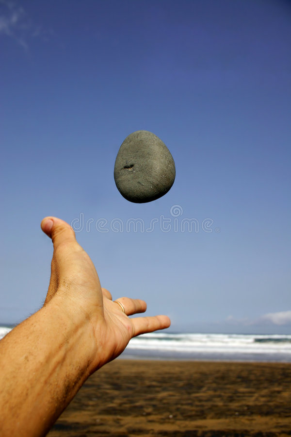 Hand Throwing Stone : Pebble and hand stock image of blue throw stone