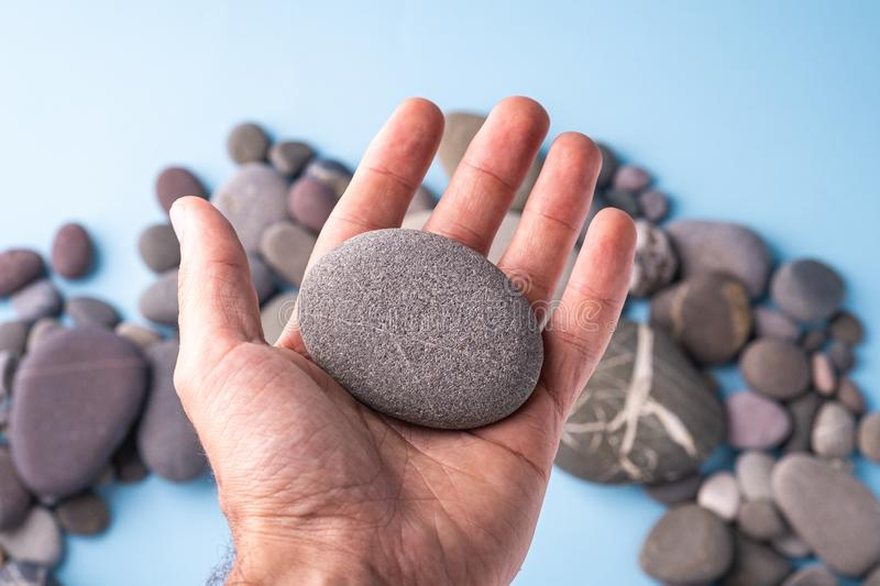 Pebble stone hold in hand on blue background with pebbles stock images