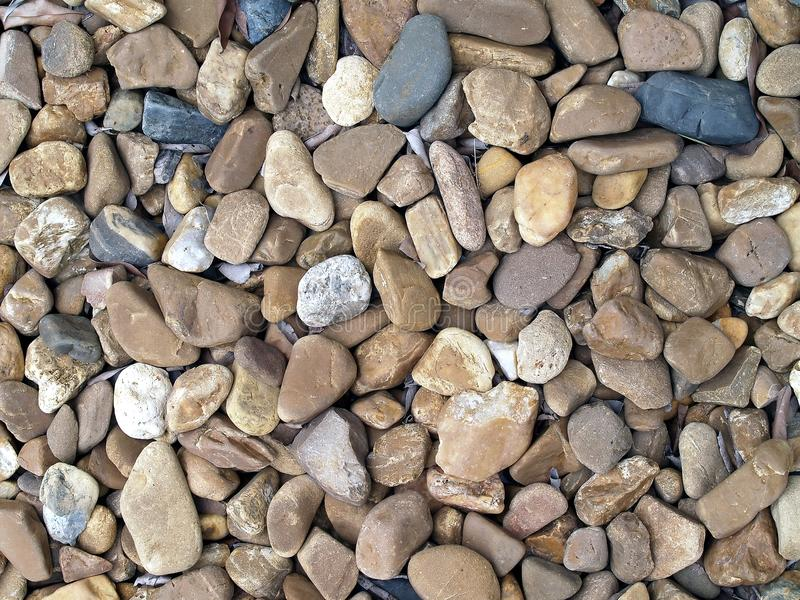 Pebble stone texture background, pile of various size of brown and black sea stones (or river stones) for garden decor. Or paving, close up top view royalty free stock photos