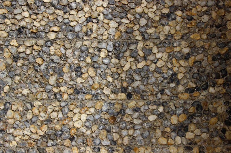 A pebble stone wall made of natural stones with one half of it in shadow royalty free stock photography