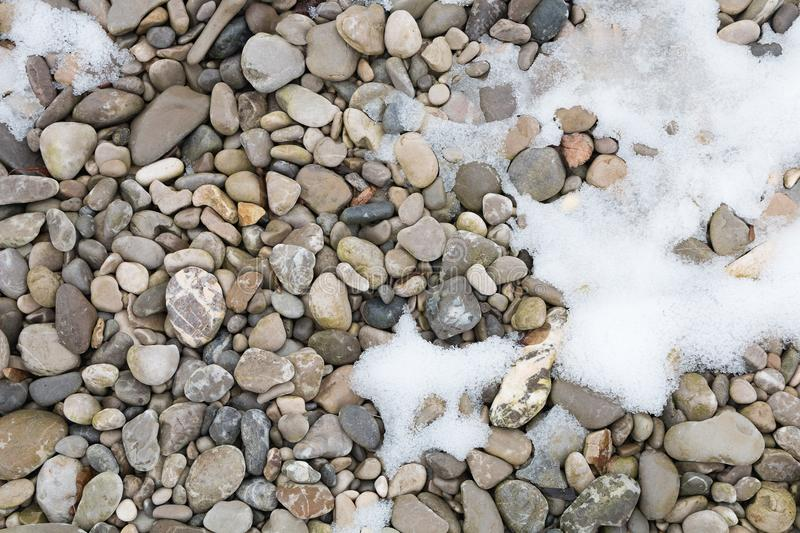 Pebble stones at the riverbank with bit of snow stock images