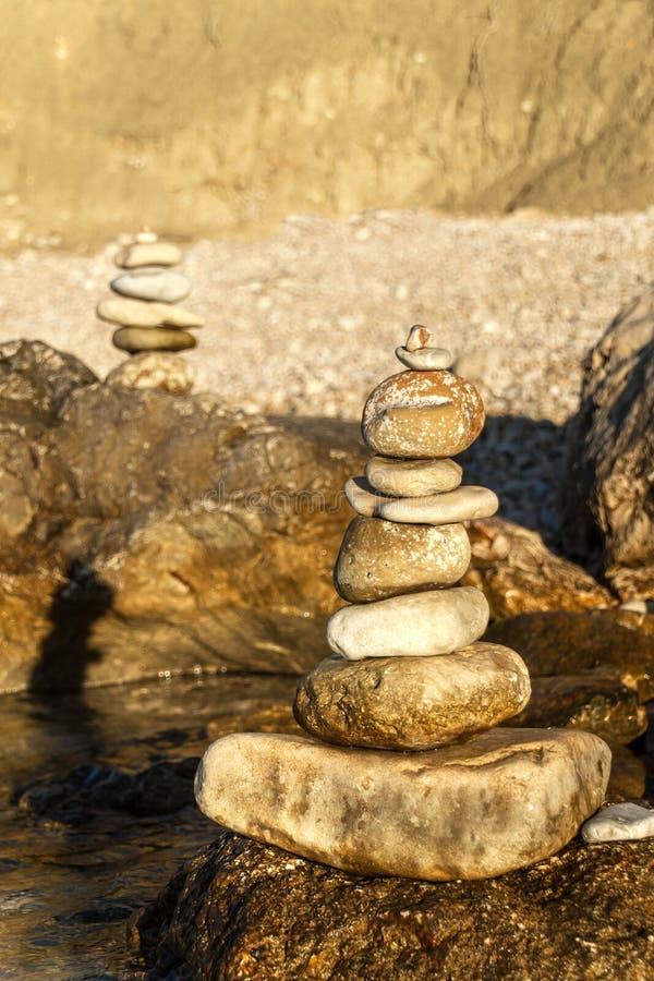 Pebblebunt på seashoren Pyramid av stenar på stranden Ljus på solnedgången Symbol av patiens Begrepp av harmoni och jämvikt fotografering för bildbyråer