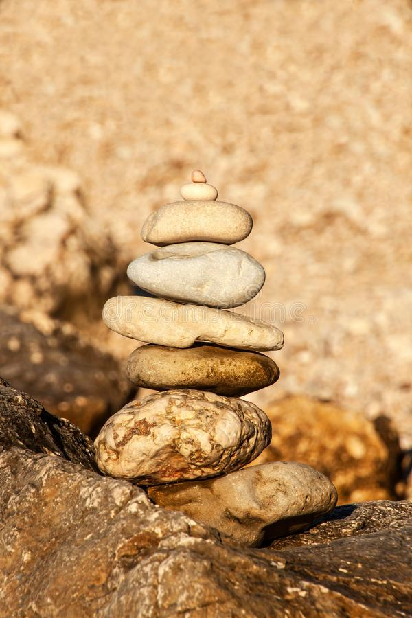 Pebblebunt på seashoren Pyramid av stenar på stranden Ljus på solnedgången Symbol av patiens Begrepp av harmoni och jämvikt arkivbild