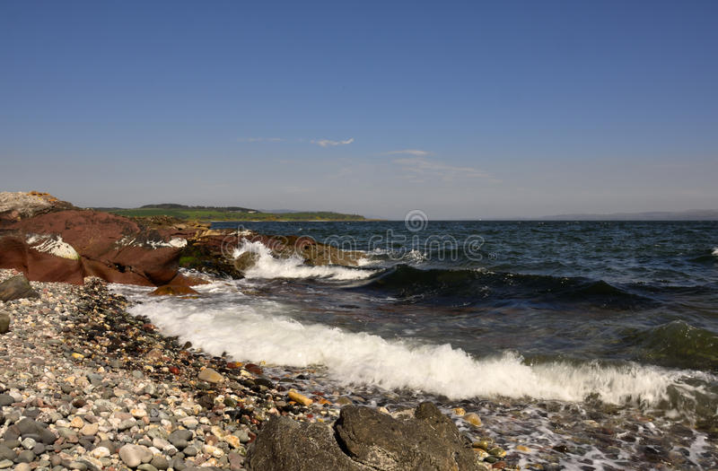 Pebbled beach, Isle of Bute. View showing motion of waves on pebbled beach, creating contrast between dry and wet pebbles, south Bute, Scotland royalty free stock images