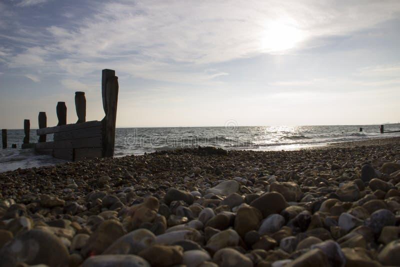 Pebbled strand på solnedgången arkivfoto