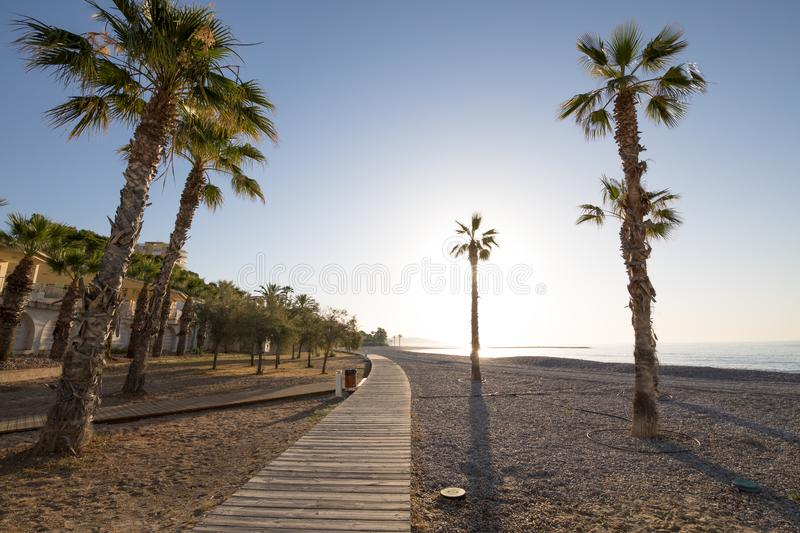 Pebbles area of Els Terrers Beach in Benicassim. Landscape Els Terrers Beach, in Benicassim, Castellon, Valencia, Spain, Europe. Wooden walkway, palm trees royalty free stock photos