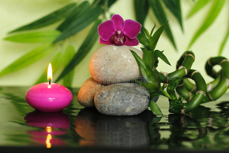 Pebbles arranged in Zen lifestyle in the center with an orchid at the top with bamboo stalks and a lighted pink candle. Pebbles arranged in Zen lifestyle in the royalty free stock photos
