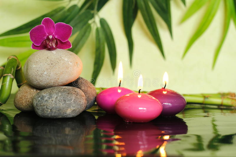 Pebbles arranged in zen lifestyle on the left with an orchid at the top and three lit pink candle. Pebbles arranged in zen lifestyle on the left with an orchid stock photo