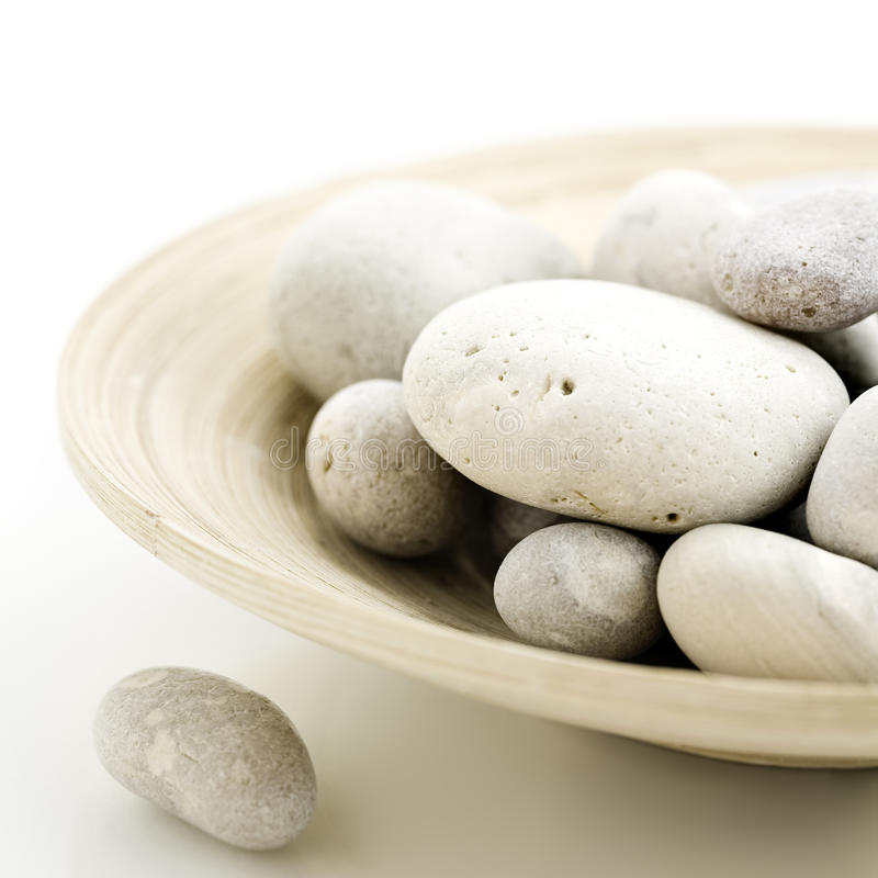Pebbles in bamboo bowl stock photo