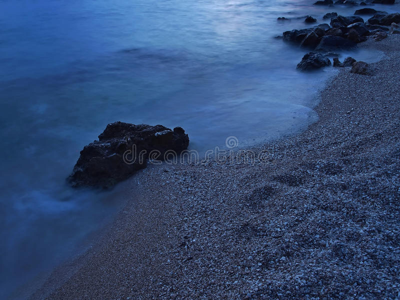 Pebbles beach at misty sea royalty free stock images