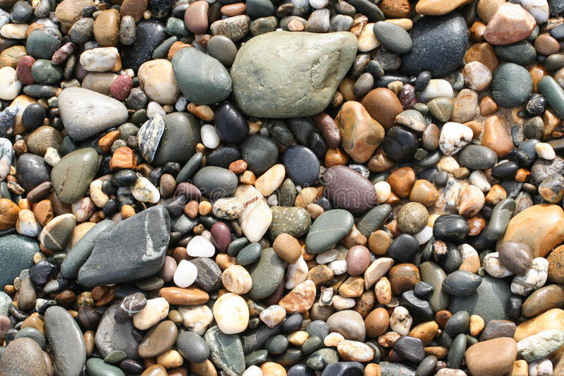 Pebbles on beach. Variety sizes and colours of pebbles lying on beach stock image