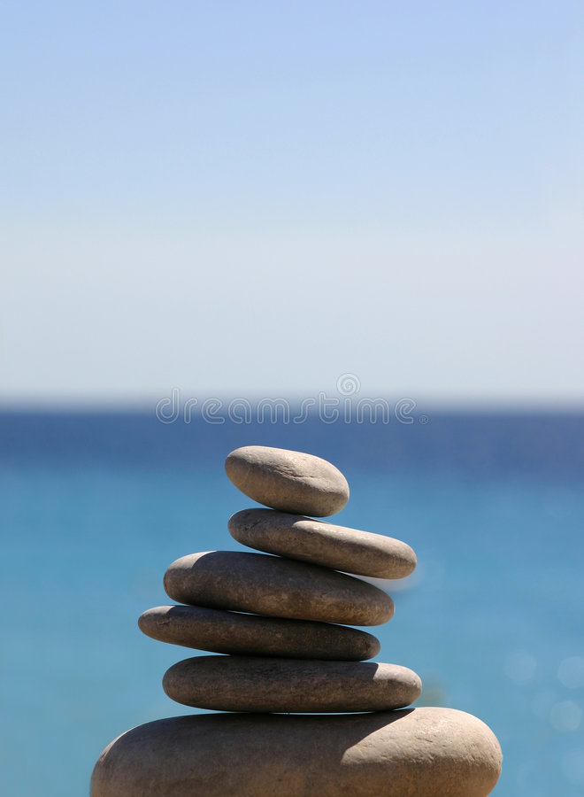 Pebbles on the blue sea and sky royalty free stock photography