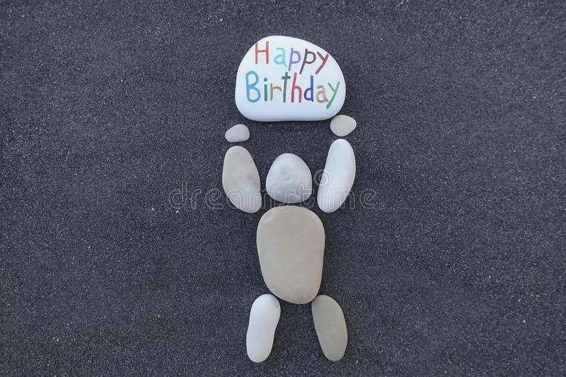 Pebbles design man holding a stone with the carved and colored message for a Happy Birthday. Happy Birthday card with a stone man holding a carved text for a royalty free stock image