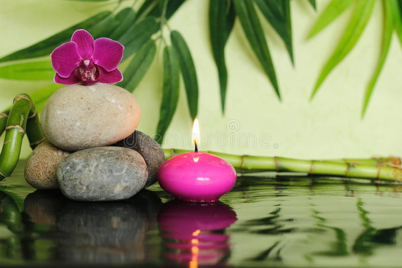 Pebbles laid on the left out in zen lifestyle with an orchid at the top and a pink candle lit. Pebbles laid on the left out in zen lifestyle with an orchid at royalty free stock photography