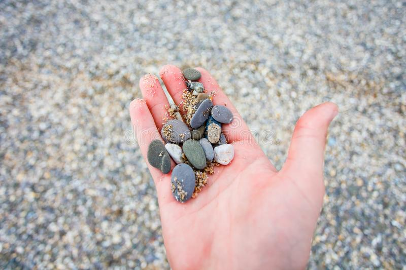 Pebbles lying in man hand close up. Travelling to sea royalty free stock image