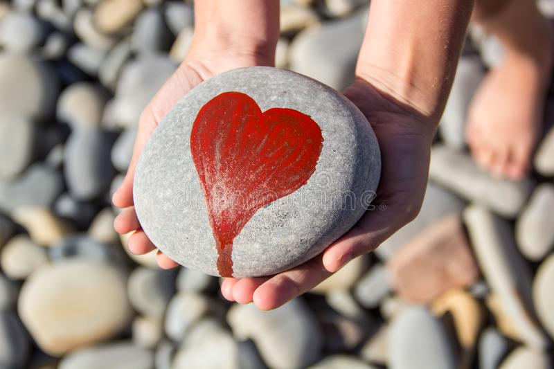 Pebbles with a painted heart in the hands of a child on the background of a pebble beach. In summer, concept, coast, love, red, abstract, affection, artwork royalty free stock photos