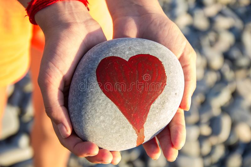 Pebbles with a painted heart in the hands of a child on the background of a pebble beach. In summer, concept, coast, love, red, abstract, affection, artwork royalty free stock image
