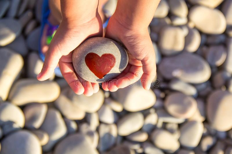 Pebbles with a painted heart in the hands of a child on the background of a pebble beach. In summer, concept, coast, love, red, abstract, affection, artwork stock image