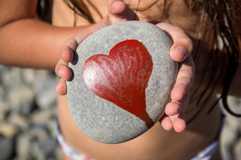 Pebbles with a painted heart in the hands of a child on the background of a pebble beach. In summer, concept, coast, love, red, abstract, affection, artwork royalty free stock images