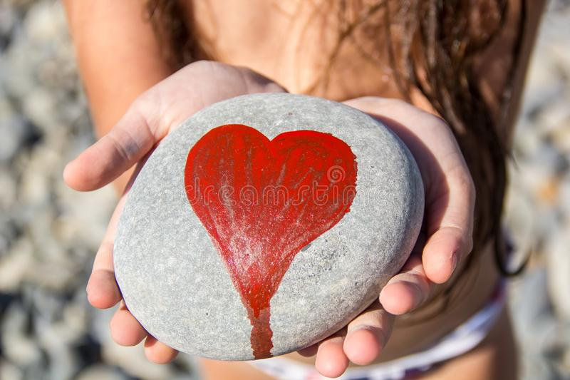 Pebbles with a painted heart in the hands of a child on the background of a pebble beach. In summer, concept, coast, love, red, abstract, affection, artwork stock photography