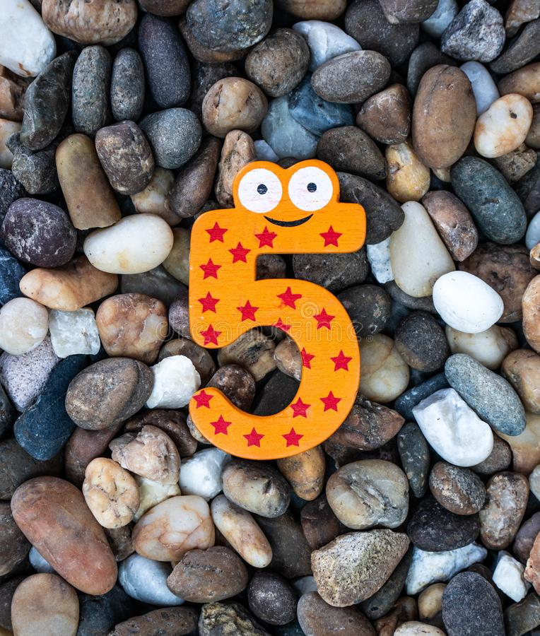 Pebbles pattern or small stones background in garden with colorful Arabic wooden numbers; 5. Concept of new year and textured. Pebbles pattern or small stones stock photography