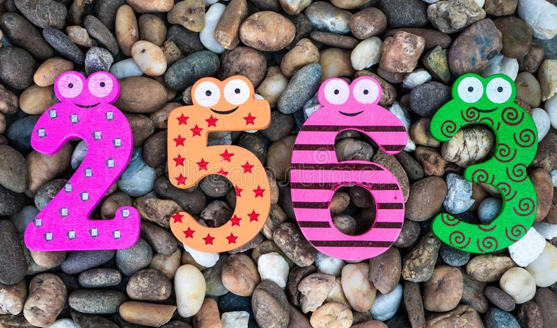 Pebbles pattern or small stones background in garden with colorful Arabic wooden numbers; 2563. Concept of new year and textured. Pebbles pattern or small stones stock images