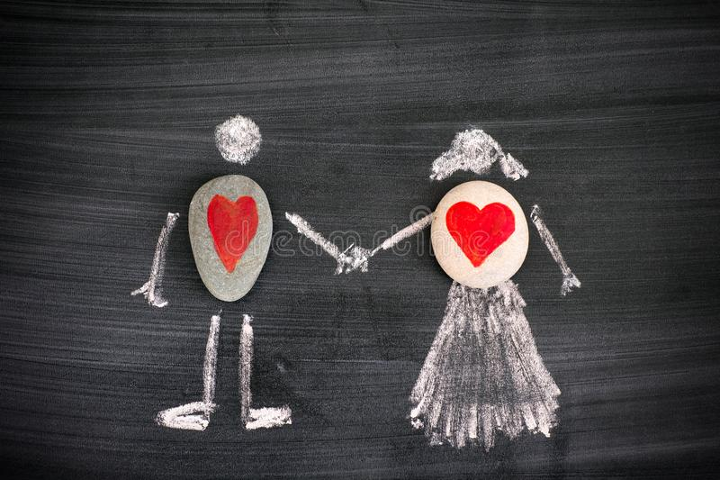 Pebbles with red hearts inside chalk drawing of man and woman on blackboard royalty free stock photography