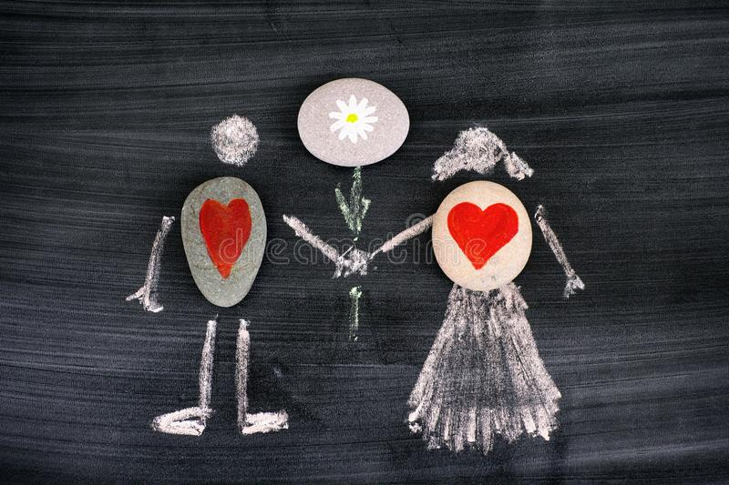 Pebbles with red hearts inside chalk drawing of man and woman holding flower in hands on blackboard stock photos