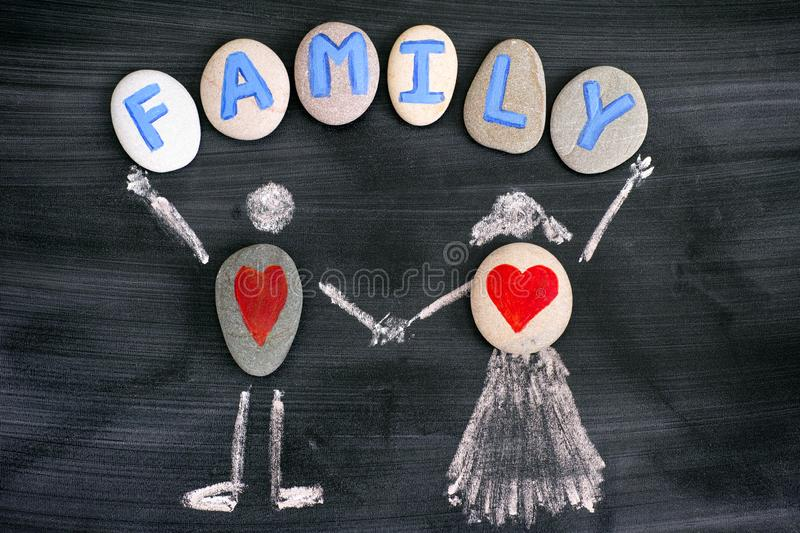 Pebbles with red hearts inside chalk drawing of man and woman and letters FAMILY on pebbles on blackboard royalty free stock image