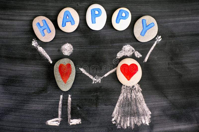 Pebbles with red hearts inside chalk drawing of man and woman and letters HAPPY on pebbles on blackboard royalty free stock photo