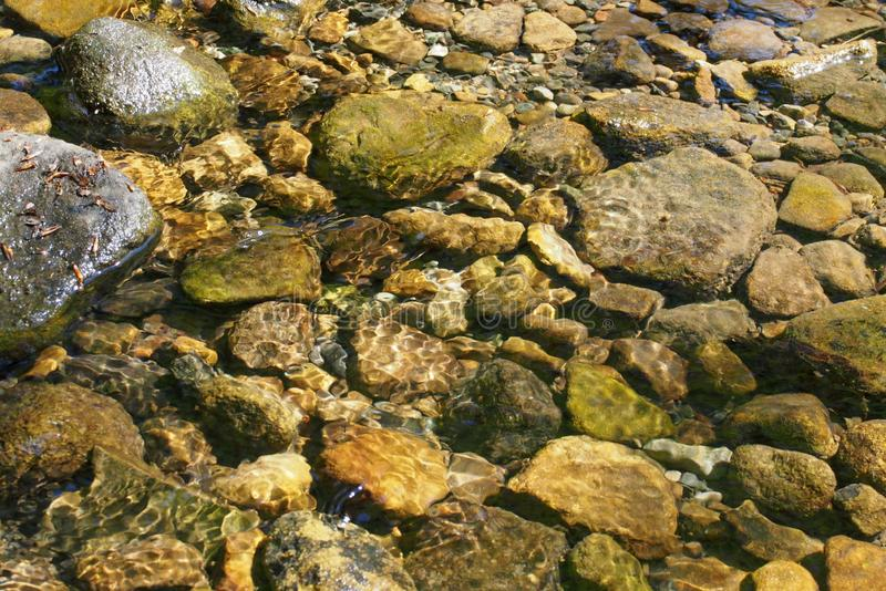 Pebbles and rocks in a shallow stream with ripples reflecting sunlight in the water stock images