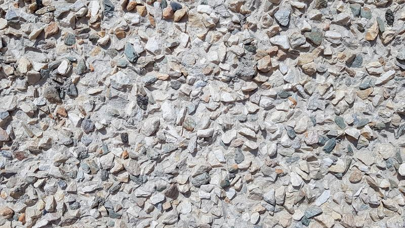 Pebbles Rubble In the cement courtyard. Dirty cracked old grunge vintage light gray concrete and cement mold texture wall or floor. Background with weathered royalty free stock images