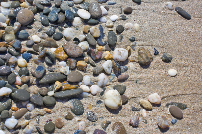 Pebbles in the sand. Texture royalty free stock photos