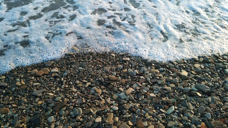 Pebbles and sea surf stock photos