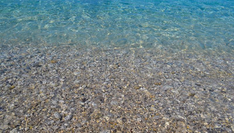 Pebbles under water. Marine background. Pure sea water. Clear sea royalty free stock image