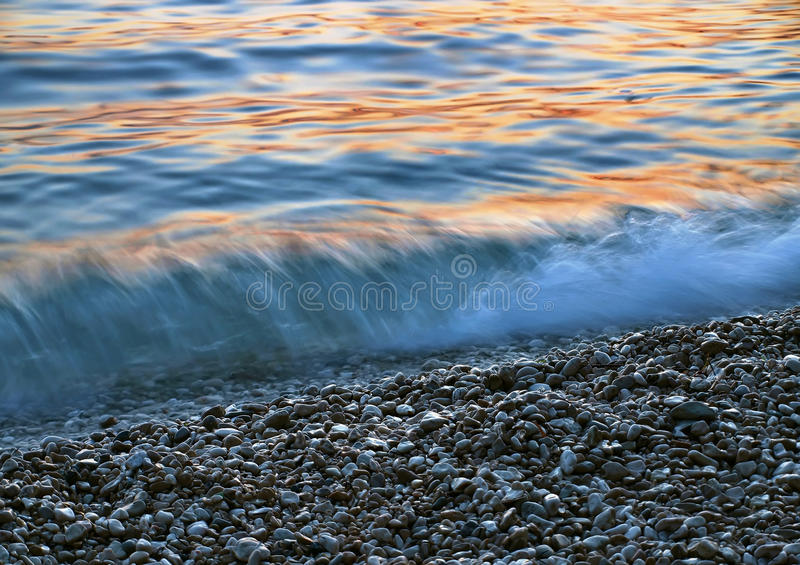 Pebbles and the waves at sunset royalty free stock image