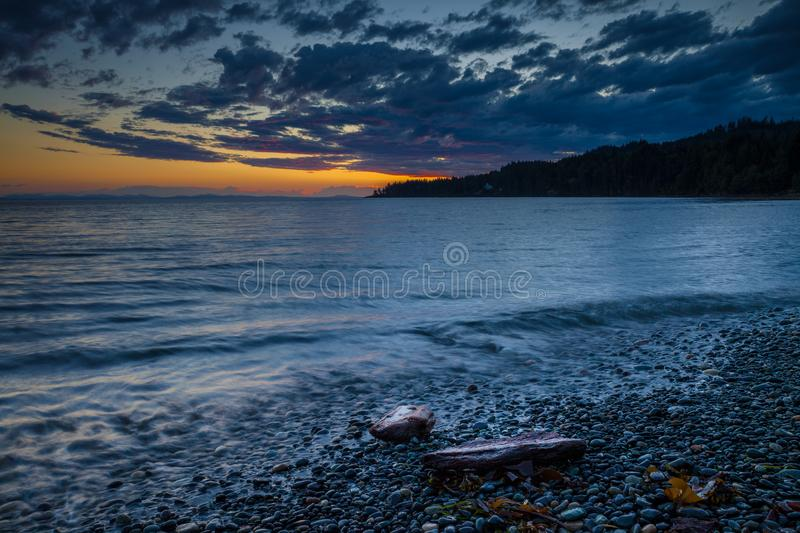 Pebbly beach on Vancouver Island at sunset royalty free stock images