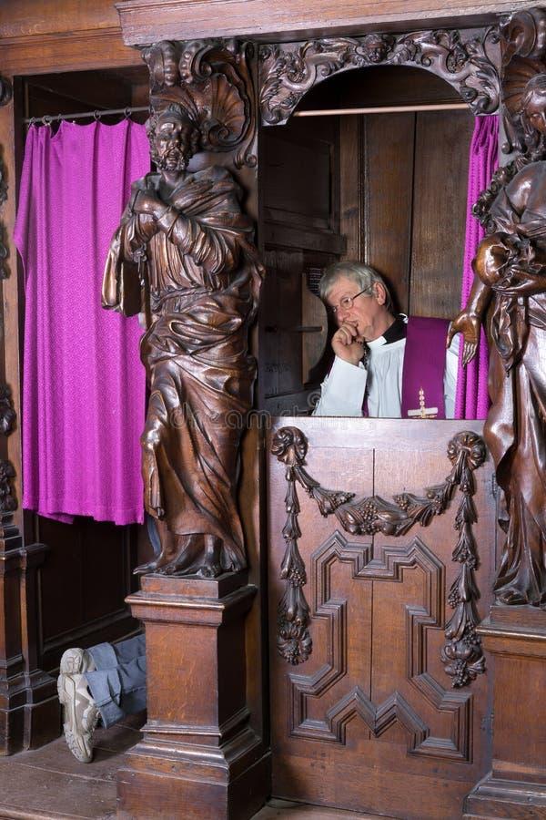 Pecador y sacerdote en cabina de la confesión fotos de archivo libres de regalías
