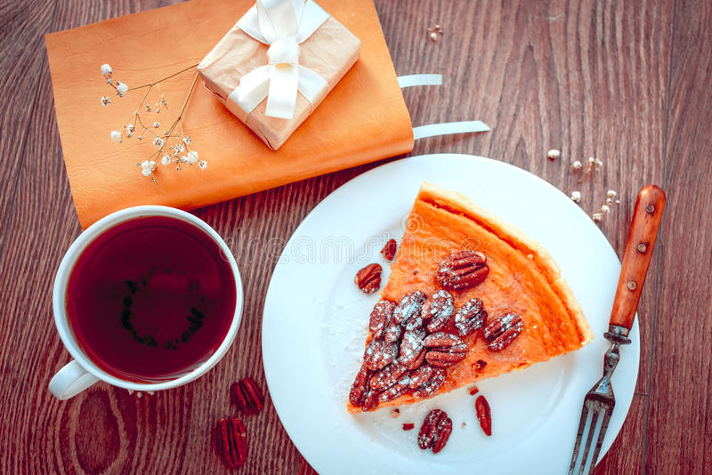 Pecan Cake. Pecan and pumpkin cake on plate with tea and books on wooden background. Toned picture stock images