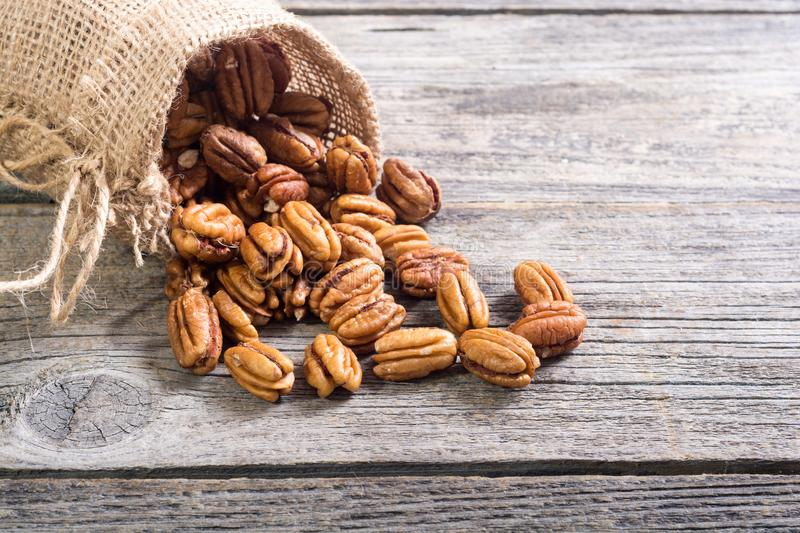 Pecan nuts in burlap bag. On wooden background . Healthy food royalty free stock photo