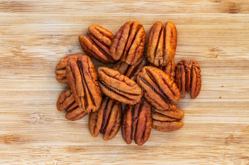 Pecan nuts in the center on a brown wooden surface. Top view, close-up stock photos