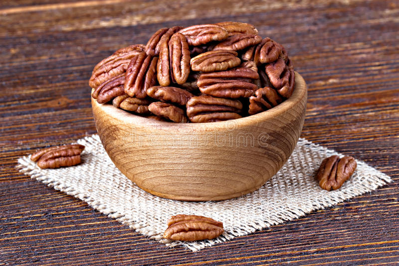 Pecan nuts. In wooden bowl over wooden backgroundselective focus royalty free stock photography