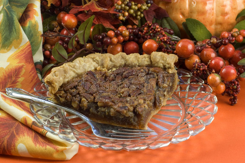 Pecan Pie. A delicious slice of homemade pecan pie on a crystal plate with fall decorations, horizontal with copy space stock photo