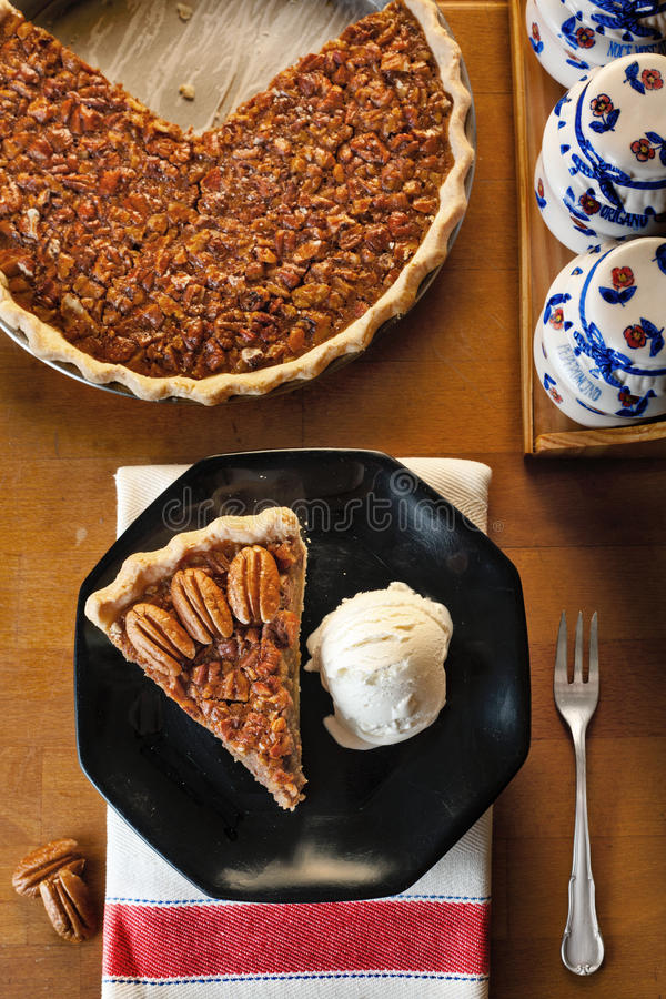 Pecan Pie. A slice of pecan pie served with vanilla ice cream on a black dish, the whole pie in the background stock photo