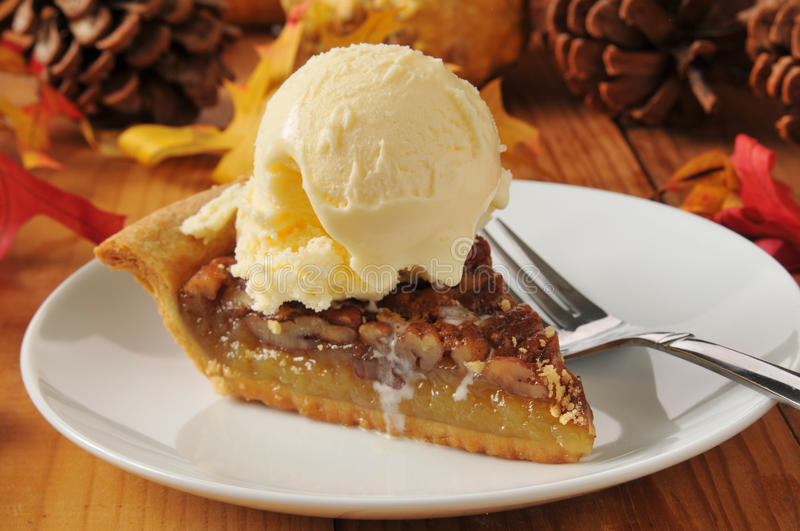 Pecan pie a la mode. A slice of pecan pie with vanilla ice cream on a colorful holiday table royalty free stock images