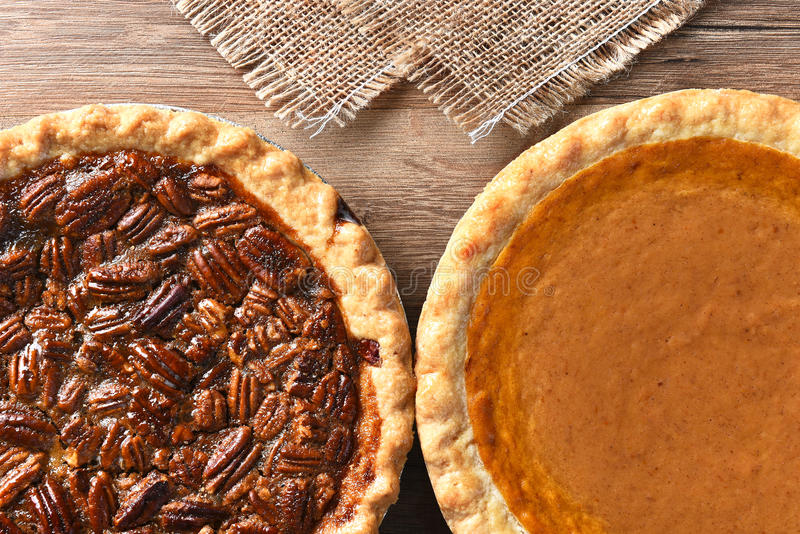 Pecan and Pumpkin Pies. Closeup of two pies on a Thanksgiving holiday table. Pumpkin and pecan pies are traditional desserts for the American holiday stock image