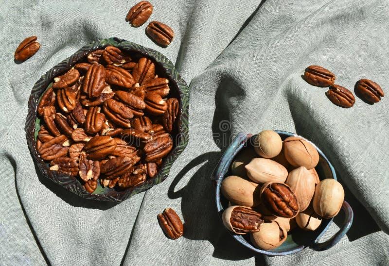 Pecannoot in ceramische kom Unpeeled noten in shell donkergroen rustiek porselein Organische ruwe gezonde voeding Hoogste dichte  stock foto's