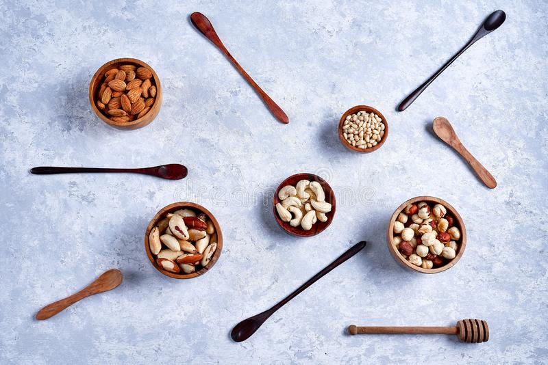 pecans, hazelnuts, almonds, pine nuts, cashews in wooden bowls on blue background, top view, flat lay stock photos
