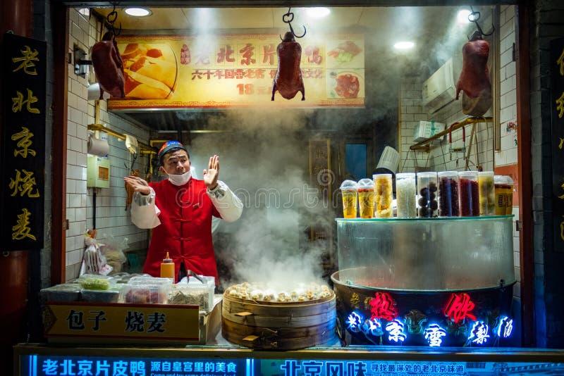 PECHINO, CINA - 20 DICEMBRE 2017: Venditore cinese del mercato dell'alimento della via di Wangfujing che vende l'anatra di Pechin immagine stock libera da diritti