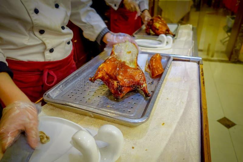 PECHINO, CINA - 29 GENNAIO 2017: Cuoco unico professionista che taglia un'anatra di Pechino tradizionale famosa facendo uso del c immagine stock libera da diritti